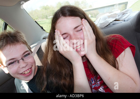 A brother and sister making funny faces in the back seat of a car, automobile. - Stock Photo