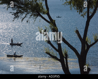 Fishermen work on Lake Atitlan, surrounded by three volcanoes in the highlands of Guatemala - Stock Photo