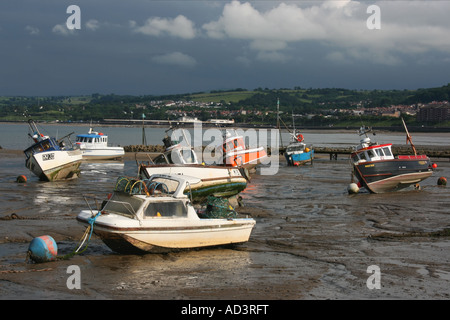 Small boats on beach  at low tide at Rhos-on-Sea harbour, North Wales - Stock Photo