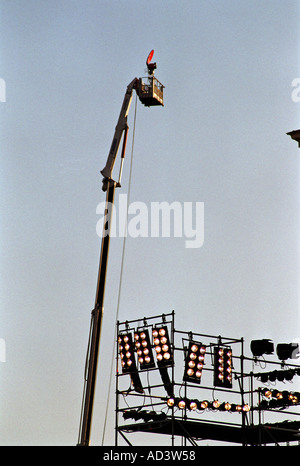 tv camera high up on top of a crane with concert lights  - Stock Photo