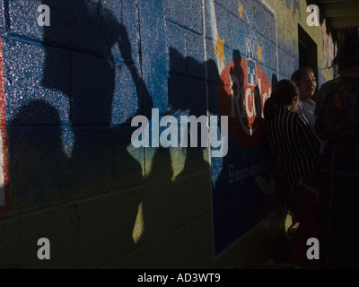 Market day as local people cast shadows on buildings facades painted with bright colors - Stock Photo