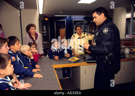 A police officer speaks to cub Scouts on a field trip to a police station  - Stock Photo