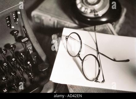 Old typewriter on desk books phone glasses horizontal - Stock Photo