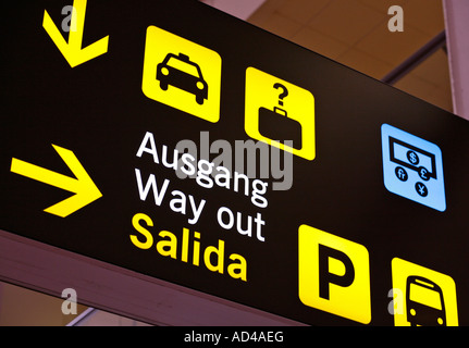 Multilingual airport sign, directions to way out, Malaga, Spain - Stock Photo