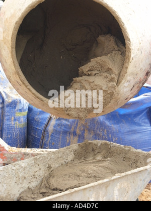 House building site close up of diesel powered cement mixer discharging bricklaying mortar into wheelbarrow - Stock Photo