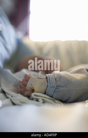 A child in a hospital bed with an IV drip in their hand - Stock Photo