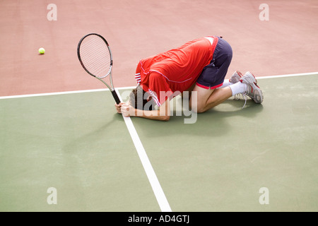 A tennis player crouching on the floor in defeat - Stock Photo