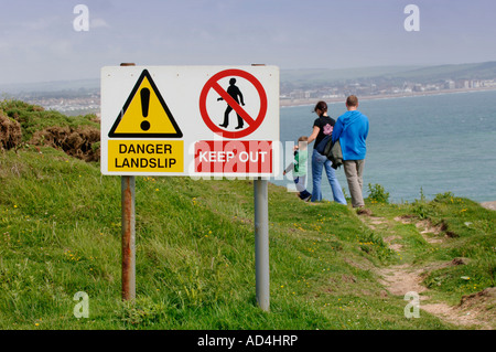 A family appear to walk beyond the danger signs on a cliff top footpath. Picture by Jim Holden. - Stock Photo