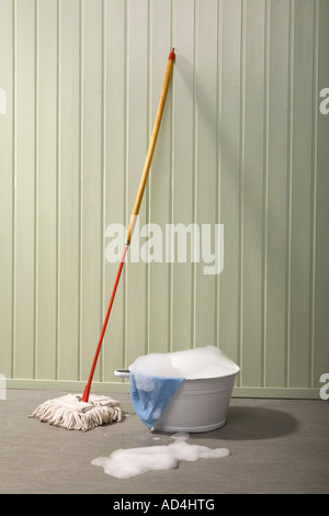 A bucket of soapy water and a mop - Stock Photo