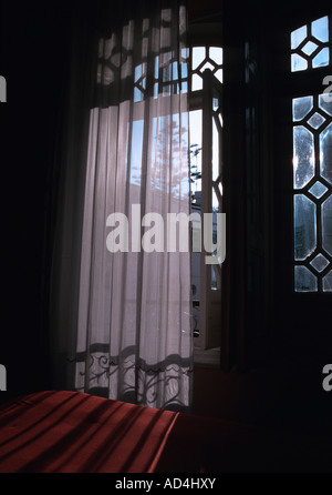 Sheer curtain in front of balcony window - Stock Photo