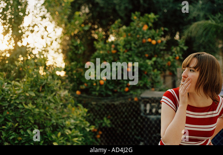 Young woman smoking a cigarette in a back yard - Stock Photo