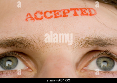 A man with 'Accepted' stamped on his forehead - Stock Photo