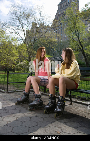 Two adolescent girls on inline skates sitting on a park bench - Stock Photo