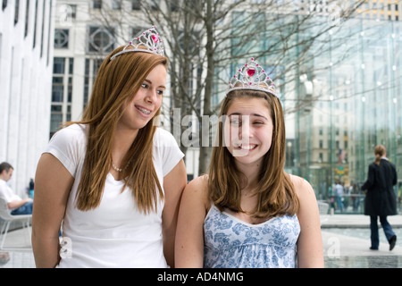Two adolescent girls wearing tiaras - Stock Photo