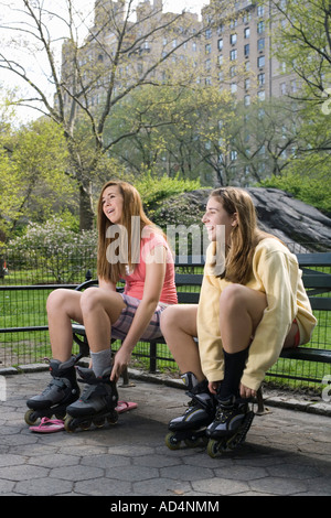 Two adolescent girls sitting on a park bench adjusting inline skates, Central Park, New York City - Stock Photo