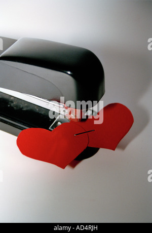Two paper hearts in a stapler - Stock Photo
