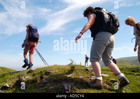 Guided walking group on rocky footpath at Castell Dinas in the Black Mountains near Pengenffordd Powys South Wales - Stock Photo