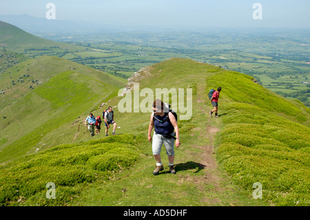 Guided walking group heading up the Dragons Back in the Black Mountains near Pengenffordd Powys South Wales UK - Stock Photo