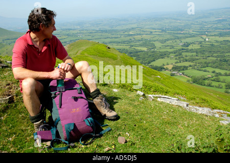 Guided walking group heading up the Dragons Back in Black Mountains near Pengenffordd Powys South Wales UK stopping - Stock Photo