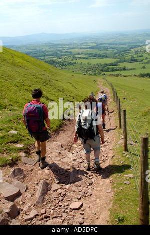 Guided walking group heading down rocky byway at Rhiw Cwnstab in the Black Mountains near Pengenffordd Powys South - Stock Photo