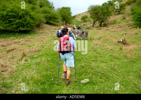 Group of walkers on footpath walking up steep slope in the Black Mountain near Abergavenny Monmouthshire South Wales - Stock Photo