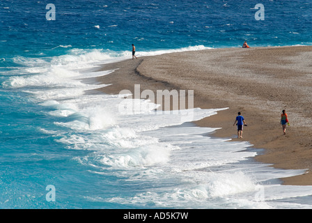 Horizontal aerial view of tourists walking along an empty beach in the early evening sunshine with waves crashing - Stock Photo