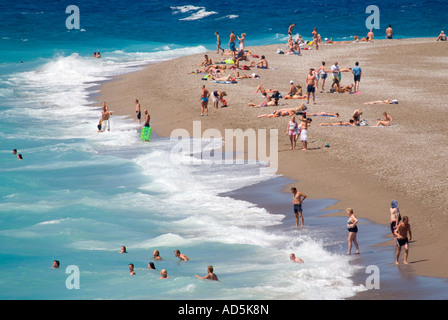 Horizontal aerial view of people enjoying themselves sunbathing on the beach and swimming in the sea in the sunshine - Stock Photo