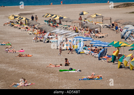 Horizontal aerial view of people enjoying themselves sunbathing on the beach. - Stock Photo
