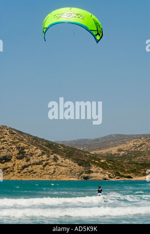 Vertical view of a caucasian man kitesurfing close to the shore in the sunshine - Stock Photo