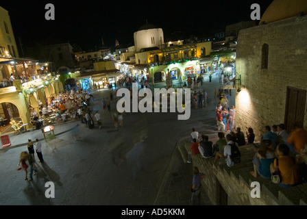 Horizontal elevated wide angle of people sitting on steps in the popular Ippokratous Square in Rhodes Old Town at - Stock Photo