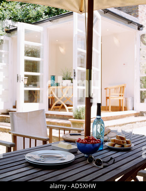 Plates and food on wooden patio table with white director s chairs and umbrella and view of modern white livingroom - Stock Photo