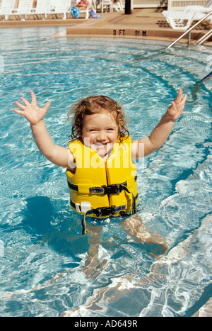 Young girl in swimming pool wearing life vest - Stock Photo