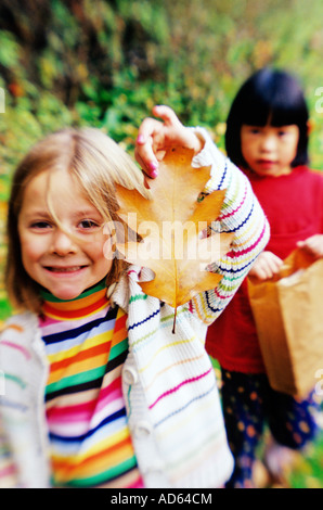 Young girl proudly holding autumn leaf - Stock Photo