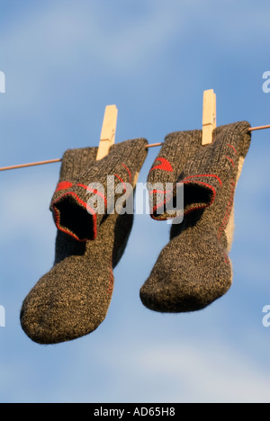 PICTURE CREDIT DOUG BLANE Concept A pair of clean grey gray and red wool walking socks hanging on a washing line - Stock Photo