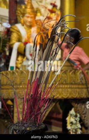 Myanmar Burma Yangon Shwedagon Paya burning incense with praying station in bkgd vertical - Stock Photo
