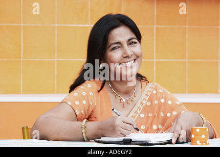 Portrait of a mature woman sitting in the kitchen holding a pen - Stock Photo