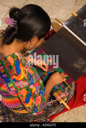 A young pretty dark skinned Cackchiquel Maya girl weaving by hand in Antigua City Republic of Guatemala Central - Stock Photo
