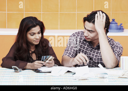 Close-up of a young couple looking at credit cards - Stock Photo