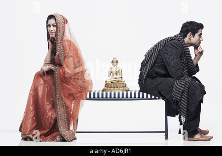 Side profile of a newlywed couple sitting on opposite ends of a bench with a statue of Buddha between them - Stock Photo
