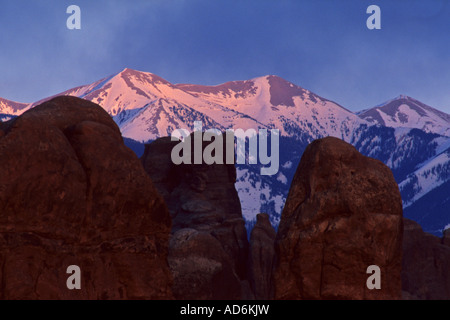 Sunset light on the LaSal Mountains during a storm as seen from Arches National Park UTAH - Stock Photo
