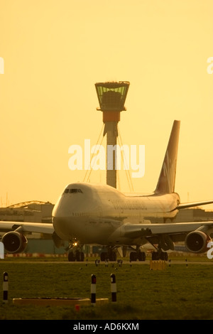 Commercial airliner and new air traffic control tower at London Heathrow Airport England UK - Stock Photo