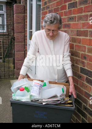 elderly woman putting out recycling bin filled with newspapers plastics for kerbside collection Worthing West Sussex - Stock Photo