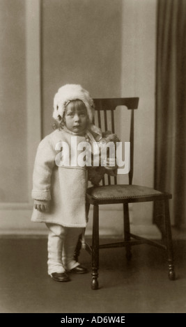 Emotive Studio portrait photo of young Edwardian girl aged 2 years called Peggy clutching a toy dog looking serious, - Stock Photo