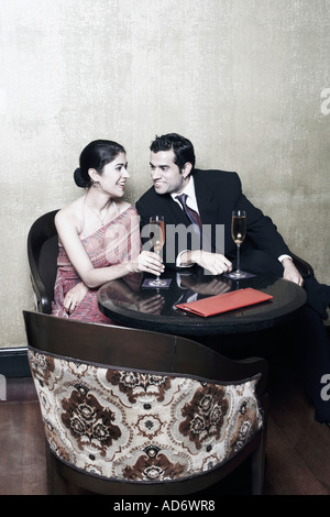 Businessman and a businesswoman sitting on chairs with champagne flutes - Stock Photo