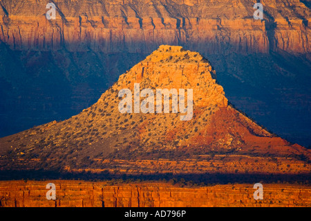 Sunrise light on red rock cliff formations below the North Rim at Point Sublime Grand Canyon National Park Arizona - Stock Photo