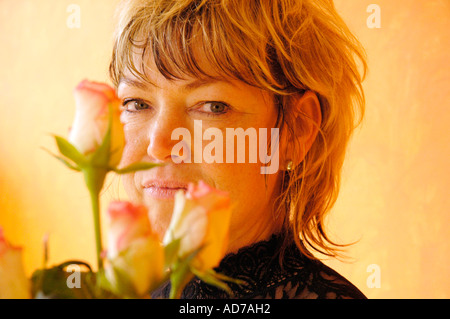 Confident pretty woman looking serious from behind a bouquet, 40, 45 years - Stock Photo