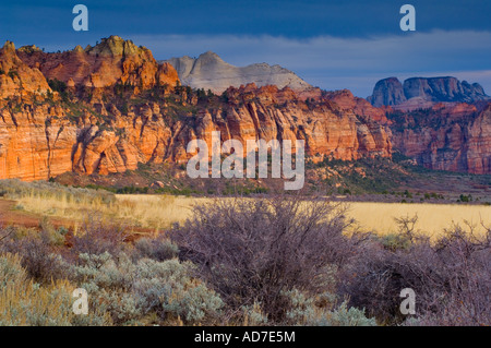 Sunset light through storm clouds on red rock cliffs near Lee Valley Kolob Section Zion National Park Utah - Stock Photo