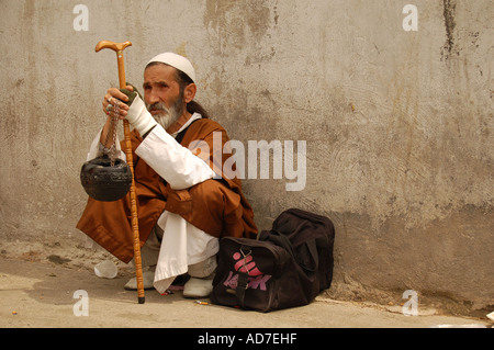 Dervish in his traditional clothes sat in the pavement in Tajrish, Tehran, Iran - Stock Photo