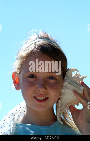 Little girl holding a seashell to her ear Listens to the sound of the seaside - Stock Photo