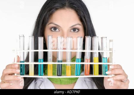 Portrait of a female technician holding a test tube rack - Stock Photo